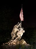 stock photo of iwo  - Statue commemorating Iwo Jima at night lit by floodlights and seen through the trees and branches - JPG