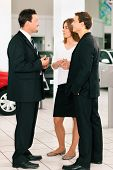 Couple with salesman at car dealer