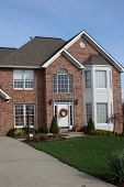 image of nice house  - section shot of new brick two story home with very green grass and wreath on door - JPG