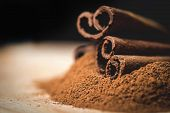 Постер, плакат: Cinnamon sticks with cinnamon powder on wooden background Selective focus