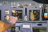 Постер, плакат: Captain Hand Accelerating On The Throttle In Commercial Airliner Flight Simulator Cockpit Thrust