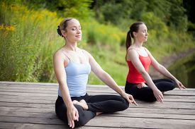 foto of pranayama  - Two serene young beautiful women on meditation session outdoors sitting cross-legged in Ardha Padmasana Posture working out in park on summer day practicing pranayama with closed eyes full length