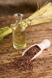 picture of flax seed oil  - Vertical photo of wooden spoon full of flax seeds placed on old wooden board - JPG