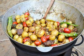 picture of cauldron  - Big cauldron with roasted potato, meat and tomato ** Note: Shallow depth of field - JPG
