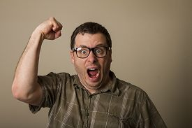 stock photo of nerds  - Nerd man with his fist up in the air and yelling as to scare someone off - JPG