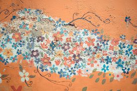 foto of mural  - Part of old flower flora mural painting pattern art on a messy crack wall texture background in vintage retro color - JPG