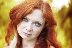stock photo of freckle face  - Portrait of redhead girl with blue eyes on nature. Face of young woman with freckles closeup ** Note: Visible grain at 100%, best at smaller sizes - JPG