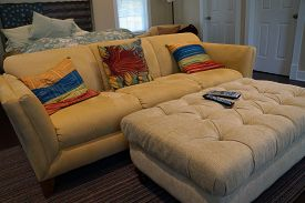 picture of ottoman  - An ottoman and a couch with pillows in a bedroom. ** Note: Visible grain at 100%, best at smaller sizes - JPG