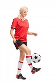 stock photo of juggling  - Full length portrait of a female soccer player juggling a ball and smiling isolated on white background  - JPG