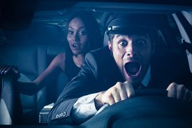 stock photo of wacky  - Male chauffeur with woman on back seat gets into car crash and makes ridiculous face - JPG