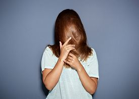 foto of incognito  - Fun portrait of a woman hiding behind her long brown hair as she pulls it down over her face with her hands upper body over grey - JPG