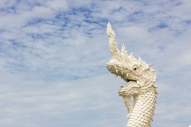 stock photo of serpent  - serpent king or king of naga statue in thai temple in background of cloudy sky - JPG