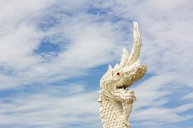 pic of serpent  - serpent king or king of naga statue in thai temple in background of cloudy sky - JPG