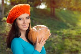 picture of beret  - Young girl with crocheted orange beret and pumpkin - JPG