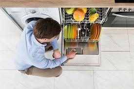 foto of detergent  - Young Man Putting Dishwasher Soap Tablet In Dishwasher Detergent Box - JPG
