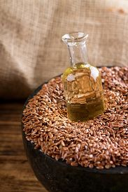 pic of flax seed oil  - Vertical photo of marble mortar bowl full of flax seeds on wooden board and with burlap in background - JPG