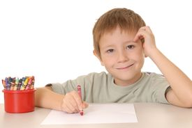 picture of school child  - young boy coloring a sheet of paper with a crayon - JPG