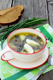 foto of sorrel  - Sorrel soup with egg and greens on a wooden background - JPG