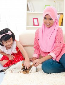 image of malay  - Malay girls playing with cat at home - JPG
