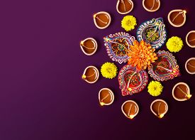 stock photo of diya  - Colorful clay diya lamps with flowers on purple background - JPG