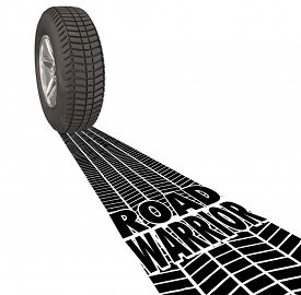 stock photo of track home  - Road Warrior words in tire tracks behind a wheel to illustrate a traveling salesperson who works away from home or traveler working outside the office - JPG
