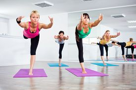 image of virabhadrasana  - Four girls practicing yoga - JPG