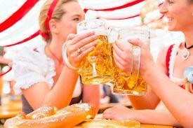 stock photo of national costume  - Friends drinking together Bavarian beer in national costume or Dirndl on Oktoberfest - JPG