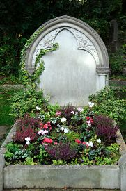 picture of life after death  - Old grave with blank headstone covered in ivy and full of flowers - JPG
