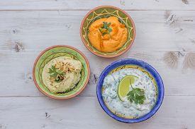stock photo of humus  - Humus and tzatziki on a white wooden table - JPG