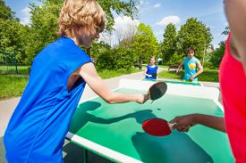 foto of ping pong  - Four international friends playing ping pong outside during summer sunny day - JPG