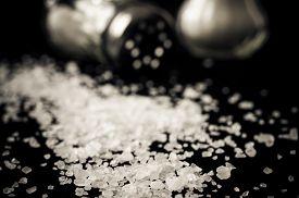 stock photo of salt shaker  - Two glass salt shakers and salt closeup - JPG