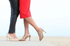 image of cuddle  - Side view of a couple of lesbian women legs cuddling with love on the beach - JPG