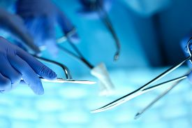 pic of surgical instruments  - Surgeons hands holding surgical instrument while operating patient in surgical theatre - JPG