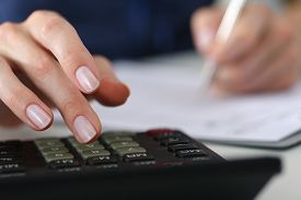 pic of economy  - Close up of female accountant or banker making calculations - JPG