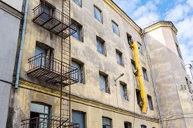 picture of reconstruction  - old building facade under reconstruction against blue sky - JPG