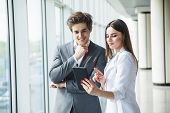 Cheerful Business Woman And Man Working Together On Tablet In Office Hall poster