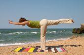 picture of virabhadrasana  - girl doing virabhadrasana yoga pose at sea coast - JPG