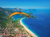 Paraglider Tandem Flying Over The Sea With Blue Water And Mounta poster