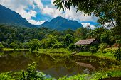 Traditional Wooden House Near The Lake And Mountain In The Background. Kuching To Sarawak Culture Vi poster