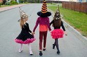 Little girls in witch costumes and hats walking away after halloween tricks poster