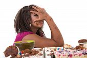 picture of bulimic  - Pretty black woman having eating a pile of sweets and now looking nauseaus - JPG