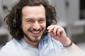 young smiling male call centre operator doing his job with a headset poster