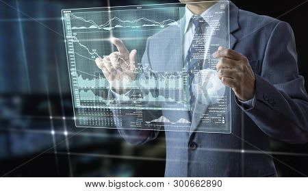 poster of Businessman Holding A Futuristic Modern Tablet Touch Screen Analysing On Investment Risk Managment A