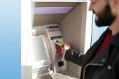 Man Inserting Credit Card Into Cash Machine Outdoors, Closeup poster