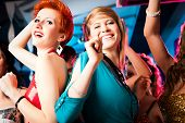 Women or models in club or disco having fun and dancing ecstatically