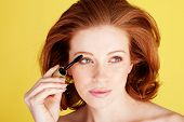 Glamorous redhead woman using a brush to apply mascara to her eyelashes