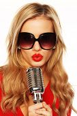 Gorgeous blonde woman wearing sunglasses with her red lips pursed in song holding a microphone