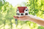mortgage, real estate and property concept - close up of hands holding house model and home keys ove poster