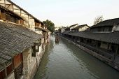 WUZHEN, CHINA - NOVEMBER 25: Tourists in a paddle boat watch local activities along the wooden houses besides the canal of this 1300 years old water town on November 25, 2011 in Wuzhen, China.