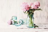 Beautiful Pink Peony Flowers In An Antique Blue Mason Jar Over A White Rustic Wood Table Background  poster